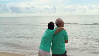 Asian senior couple walking happily by the beach. Well plan retired lifestyle no financial problem