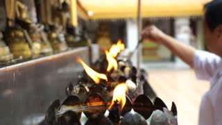 Asian senior doing Buddhist ritual pouring oil to fill candle flame for Buddha statue