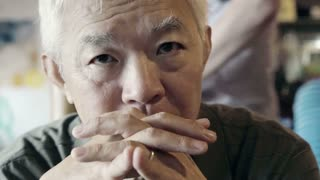 Asian senior guy with hand on face and thinking