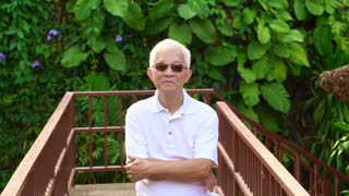 Asian senior man at wood deck with green background