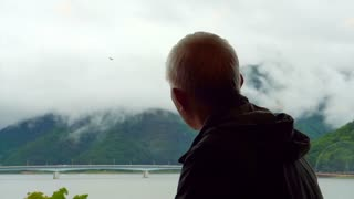 Asian senior man sitting alone and look out to mountain and lake view