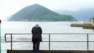 Asian senior man standing alone at the beach front pier in gloomy rainy day