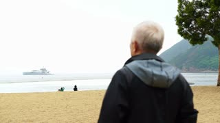Asian senior man standing alone at the beach front