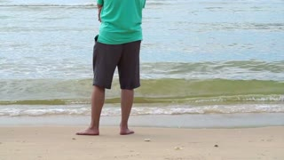 Asian senior man standing alone at the beach thinking about life