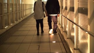 Asian senior retired couple walking holding hands along the cover walkway from train station to condominium