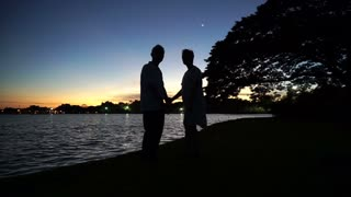 Asian senior silhouette holding hand next to lake. Early morning before sunrise. Beautiful nature