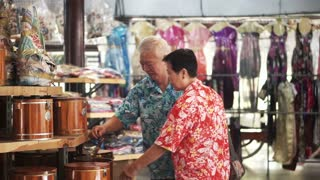 Asian senior tourist walking and shopping for local craft in Thailand