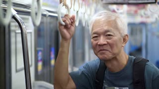 Asian Senior travel backpack in Japanese train for holiday