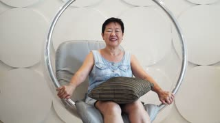 Asian senior woman sitting and relaxing at lounge on transparent floating ball chair