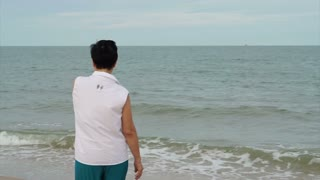 Asian senior woman walking alone along the beach enjoying nature