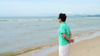 Asian senior woman wearing sunglasses and thinking about life planning next to the sea