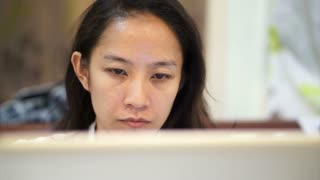 Asian woman girl working concentrated behind laptop computer