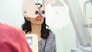 Asian woman having her eyes sight examined checked by doctor, Optometry concept