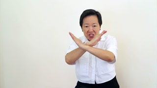 Asian woman Senior looks at camera shakes head and do hand gesture to decline, says no