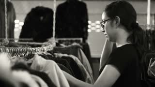 Asian woman shopping, choosing clothes on rack in black and white video