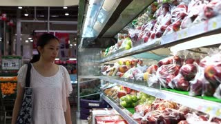 Asian woman shopping for fruits in supermarket isle