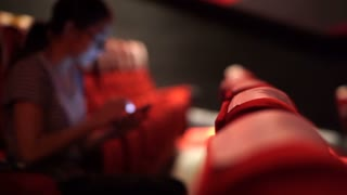 Asian woman using smart phone in cinema movie theater, bad habit of social media addiction