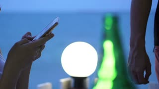 Asian woman with smart phone during dusk at blue ocean beach