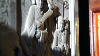 bas relief art work with morning sun light in Chinese temple. Religious art details