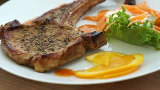 battered fish steak and grilled pork chop steak with bone. colourful salad and vegetable