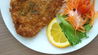 battered fish steak with colourful salad and vegetable