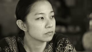 beautiful Asian woman sitting and thinking in black and white
