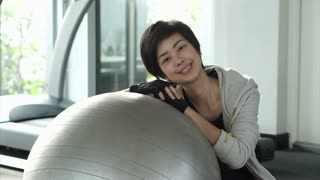 Beautiful fit Asian girl with pilates ball in gym