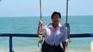 Beautiful senior Asian woman relax on the swing at the beach with blue sea background