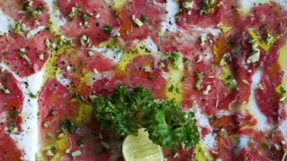 Beef carpaccio appetizer dish, sliced raw beef with olive oil, garlic and lime close up texture