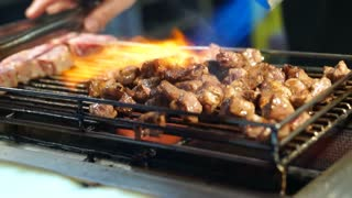 Beef steak dice cooking and flamed on bbq grill oven. Street food vendor in Taiwan