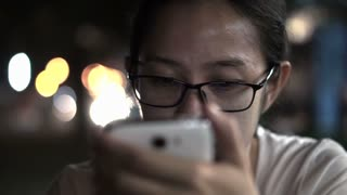 Black and white glassed Asian women texting using smart phone with city at night light background