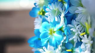 Blue and white artificial flower aloha hanging next to tropical pool