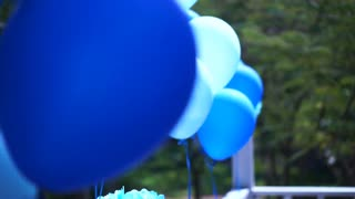 Blue party balloons floating at outdoor terrace, fun and bright day for celebration