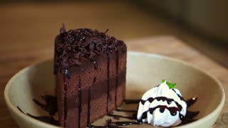 Brown thick chocolate fudge cake serve with whipped cream on wooden plate