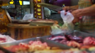 Butcher selling fresh meat in local Asian market, unhygienic food preparation