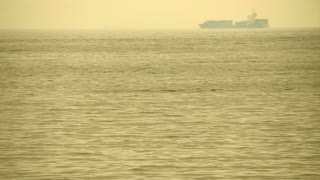 Cargo freighter ship sailing, moving at ocean horizon golden sky in hazy sea