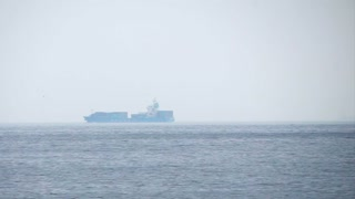 Cargo freighter ship sailing, moving at ocean horizon sky in hazy sea