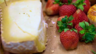 Cheese with strawberry, berries and fruits on wood platter