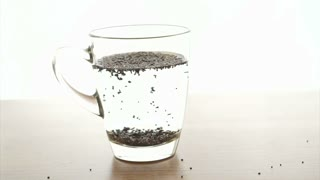 Chia seeds soaked up in water glass on white background