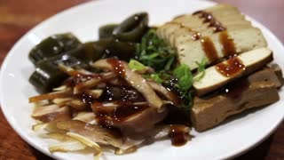 Chinese Taiwanese noodle shop side dishes. Soy tofu, seaweed, pig's ear, vegetable and oyster sauce topping