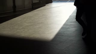 City people walking to commute in morning sunlight casting shadow on paving floor