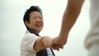 Close up shot of senior asian couple holding hands with wedding rings on man hand