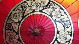 Close up shot of traditional hand made Asian red umbrella oriental style. Travel to Asia abstract background
