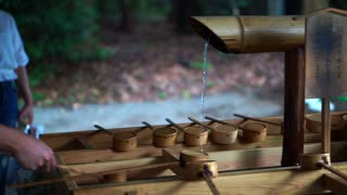 Closeup video of hands of people taking water with bamboo ladle to clean their hand before entering Japanese temple