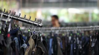 Clothes rack rows with lot of dress and shirt hanging for sale in second hand warehouse shop