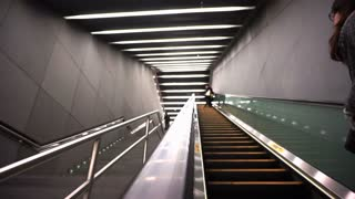 Commuter riding escalator at subway station POV on a modern architecture