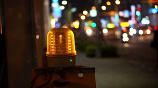 Construction warning light blinking for night time site in city traffic blur background