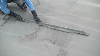 Construction worker plastering to smooth wet cement floor by using tool for large area