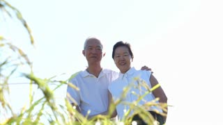 Cool Asian senior couple enjoying sunshine in nature meadow field on white shirts