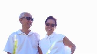 Cool Asian senior couple enjoying sunshine in nature wearing sunglasses and white shirts